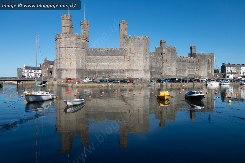 Caernarfon Castle reflected in the water of Afon Seiont at high tide, with local boats floating in the waters.
