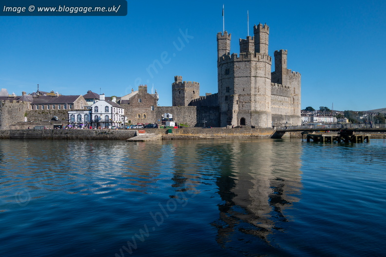 Caernarfon Castle and the waterfront is reflected in the Menai Strait