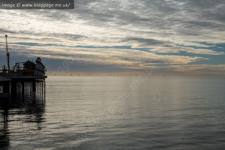 A view from January of a calm sea off the Palace Pier in Brighton with the Rampion Windfarm visible in the distance.
