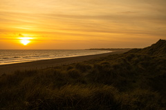Sunset over the Sand Dunes -- The Sun sets into the sea off the Sussex Coast at Littlehampton as viewed from the Sand Dunes on West Beach.