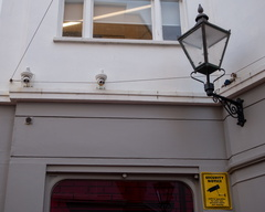 Brighton CCTV -- An image of a shop front in Brighton with the old gas lamp style street light contrasted with the CCTV everywhere on the shop front.