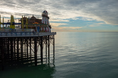 Empty Pier -- The Palace Pier in Brighton is empty during the Winter season with no tourists in sight. The sea ripples underneath the pier and the Rampion Windfarm is visible on the horizon.