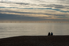 Rampion Wind Farm -- A couple sits on Brighton beach looking out at the Rampion Wind Farm which sits off of the Sussex Coast just south of Brighton. This view on a calm day shows the wind farm with clouds drifiting overhead.